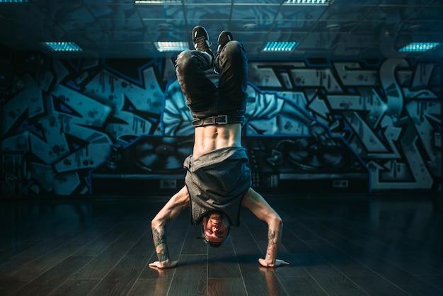 Молодой исполнитель брейк-данса, движение вверх ногами. современный городской танцевальный стиль. мужчина танцор
