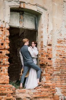 Молодая пара жениха и невесты нежная, держа друг друга. летняя свадьба, рыжая женщина и мужчина.