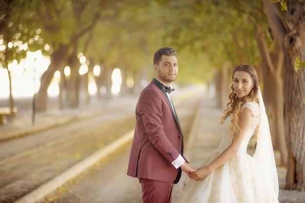 Молодые невеста и жених в свадебном платье и причинная свадьба