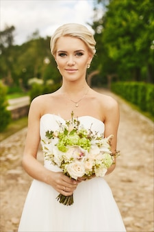 Young bride, beautiful blonde, model girl with blue eyes with flowers in the hands, outdoors