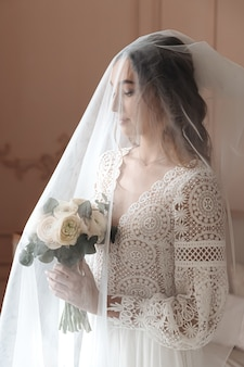 Young bride in a beautiful boho lace dress under a long veil.