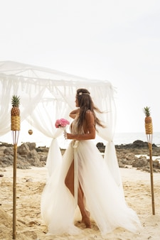Young bride in beautiful wedding dress on the beach