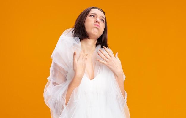 Giovane sposa in bellissimo abito da sposa che alza gli occhi infastiditi e annoiati in piedi sull'arancia