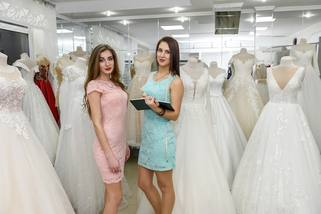 Young bride booking wedding dress in dealer in salon