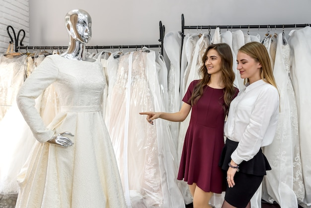 Young bride choosing dress for wedding ceremony