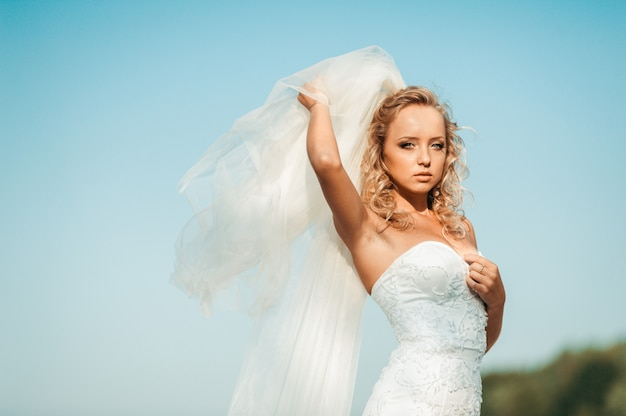 Young bride in a dress on a background of blue sky