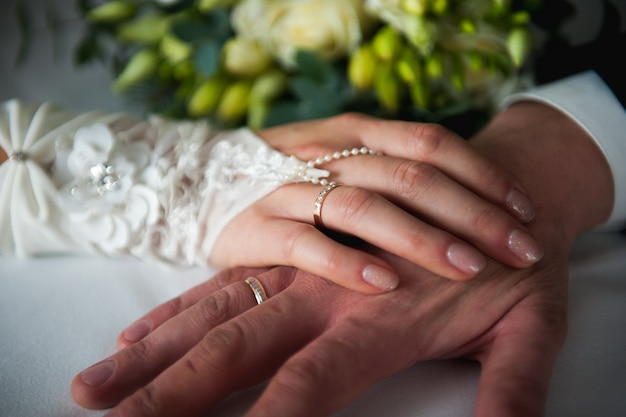 Young bride and groom hand gently touch each other close-up