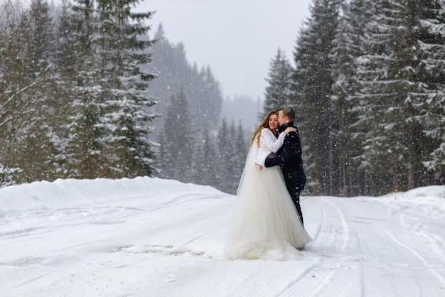 Young bride and groom on the snowy forest