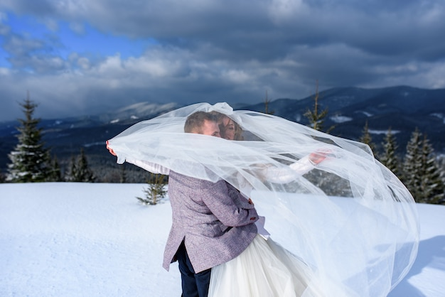 Young bride and groom on the snowy mountain