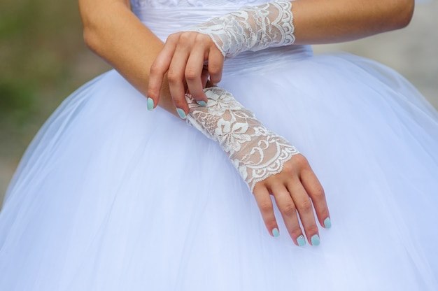 Young bride hands with beautiful manicure dress gloves