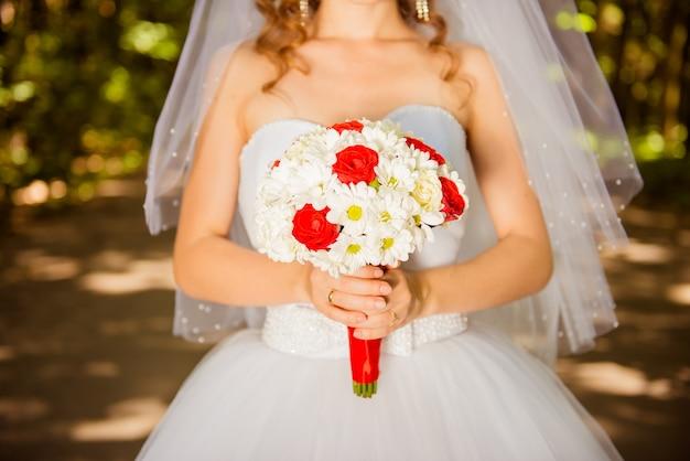 Молодая невеста держит свадебный букет