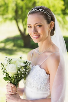 Young bride holding bouquet in garden