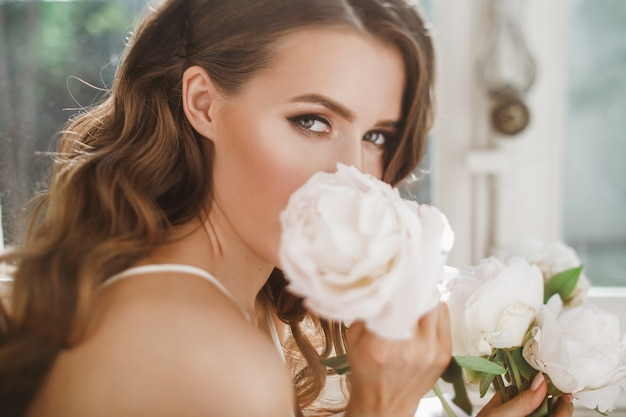 Young bride holds a bouquet of peonies siting on the windowsill in the bright morning