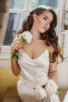 Young bride holds a bouuqet of peonies siting on the windowsill in the bright morning