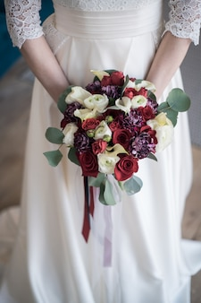 Young bride holds spring wedding bouquet