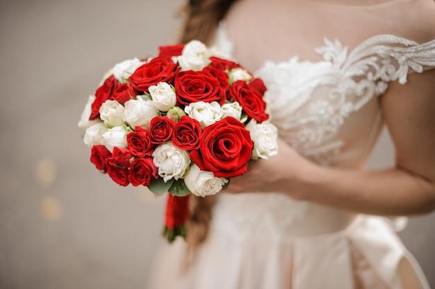 우아한 흰색과 붉은 장미 꽃다발을 들고 웨딩 드레스에 젊은 신부