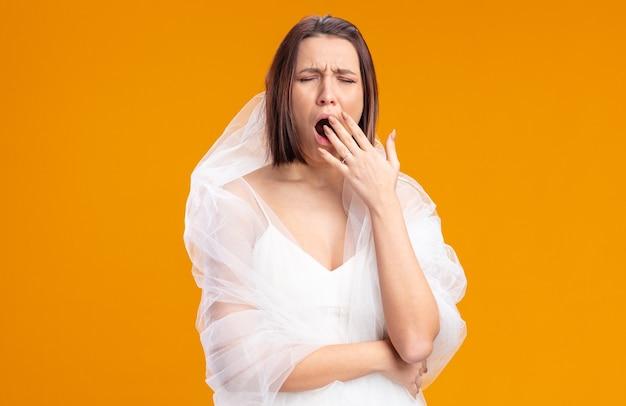 피곤하고 지루해 보이는 아름다운 웨딩 드레스를 입은 젊은 신부가 주황색 벽 위에 손으로 입을 가리고 하품을 하고 있다