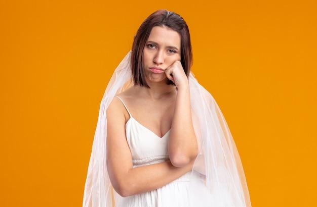 オレンジ色の上に立って疲れて退屈な美しいウェディングドレスの若い花嫁