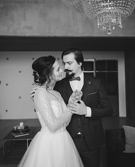 古典的なスーツのハンサムな新郎とレースのドレスの若い花嫁。屋内ポートレートカップル
