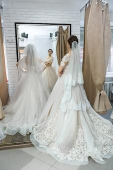 彼女の反射を鏡で見ているサロンの若い花嫁