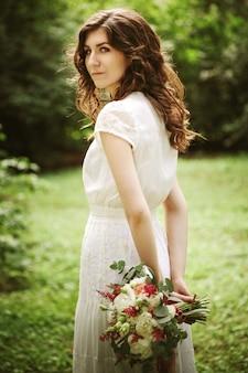 Молодая невеста в парке с цветами в руках