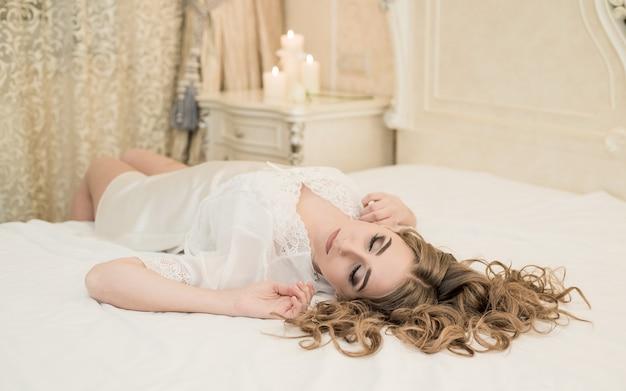 Молодая невеста в белом кружевном будуаре