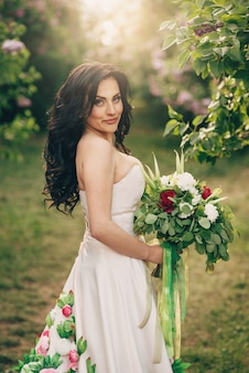 Young bride in a luxurious dress of flowers is standing in a blooming lilac garden