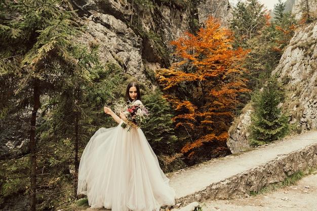 山を背景にポーズをとる若い花嫁。