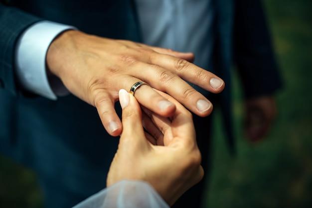 若い花嫁が新郎の指に金の結婚指輪を置く