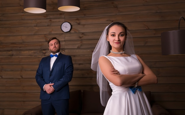 Young bride and serious groom on wooden room