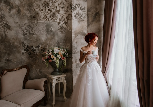 A young bride stands by the window and drinks coffee. wedding theme