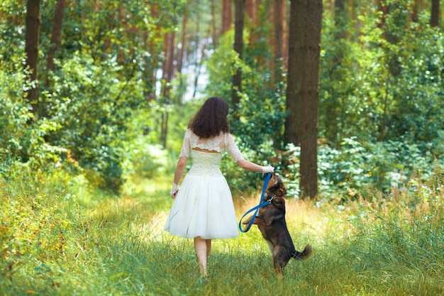 Молодая невеста гуляет с собакой по сельской дороге