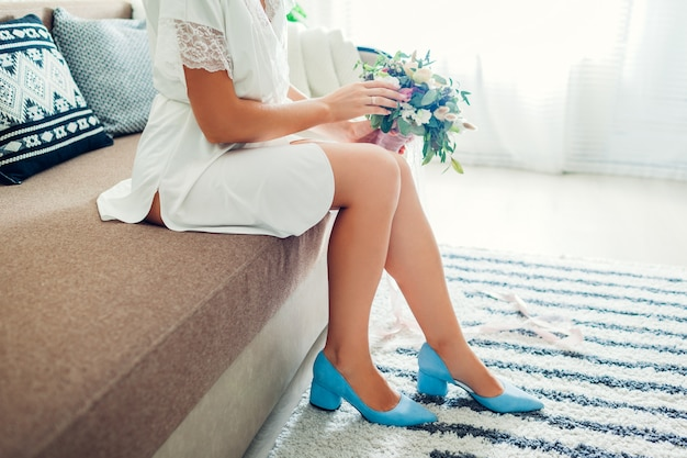 Young bride wearing silk dressing gown and blue shoes and holding bouquet at home. wedding day