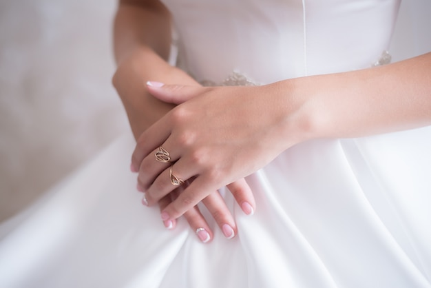 Young bride in wedding dress gently holding her hands with fingers with a ring