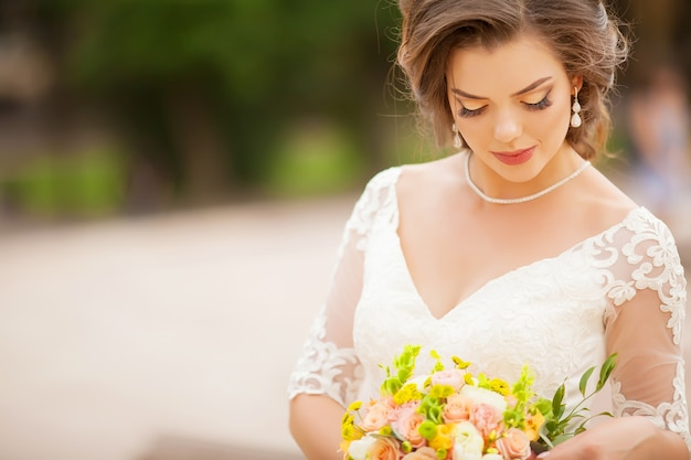 Young bride in wedding dress holding bouquet, portrait