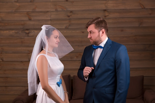 Young bride in white dress and veil against serious groom in suit on wooden room