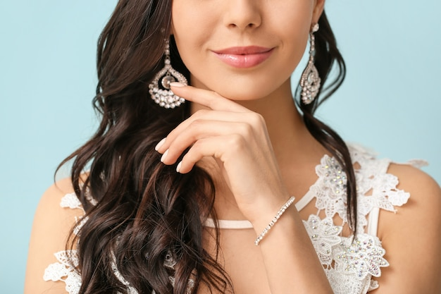 Young bride with beautiful jewelry on color surface