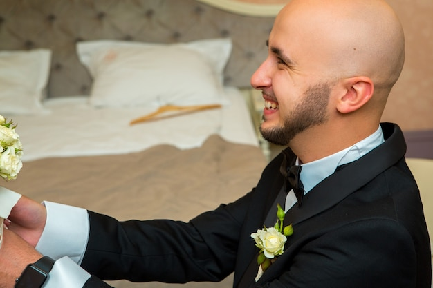 Young bridegroom smiling and looking aside at home