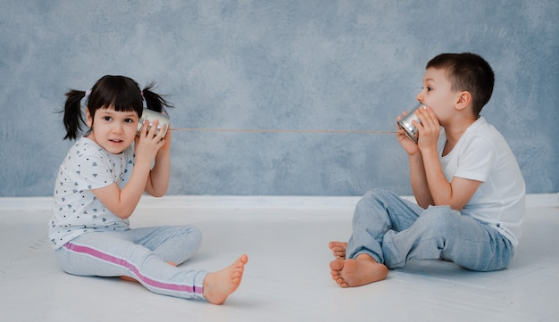 A young brother and sister are talking to a tin phone against a gray wall.