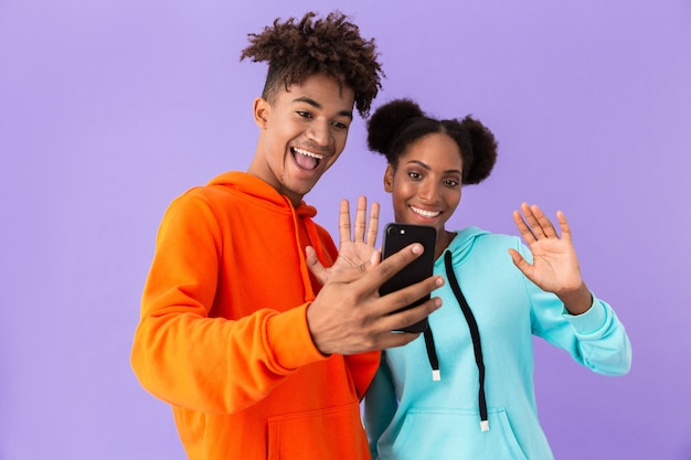 Young brother and sister wearing colorful sweatshirts using mobile phone, isolated over violet wall