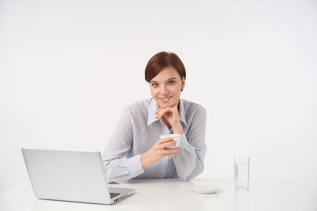 カジュアルな髪型の若い茶色の目の短い髪のブルネットの女性は、上げられた手で彼女のあごを傾けて、セラミックカップで白でポーズをとって、気持ちよく笑っています