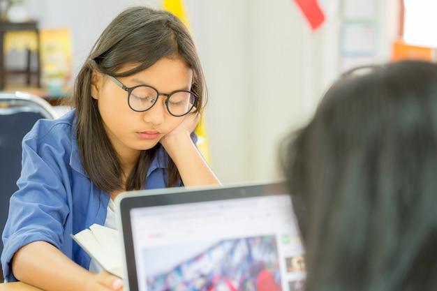 Молодая коричневая женщина волос в очках читает книгу