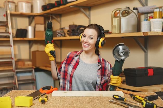格子縞のシャツ、灰色のtシャツ、遮音ヘッドフォン、さまざまなツール、電動のこぎり、電気ドリルで木製のテーブルの場所で大工仕事のワークショップで働いている黄色い手袋の若い茶色の髪の女性。