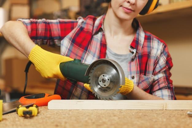 格子縞のシャツ、灰色のtシャツ、遮音ヘッドフォン、さまざまなツールを使用して木製のテーブルの場所で大工のワークショップで働く黄色の手袋、パワーソーで木材を鋸で挽く若い茶色の髪の女性