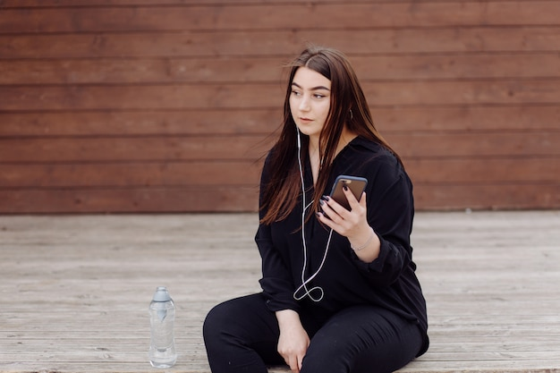 Young brown hair woman with laptop and smart phone computer sitting on wood floor