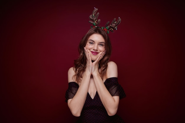 Young brown haired attractive female wearing evening makeup during chrismas party, holding her cheeks with raised palms and having fun