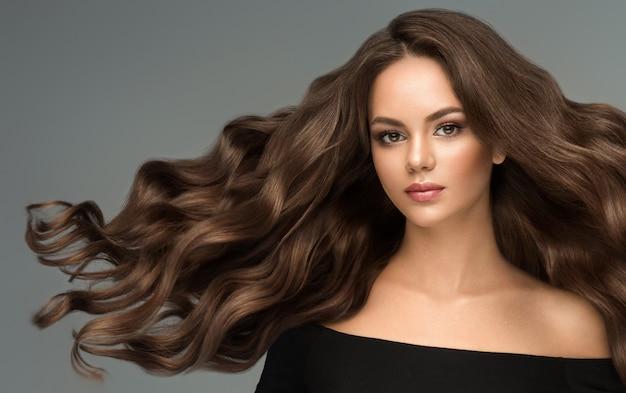 長い巻き毛の手入れの行き届いた髪とエレガントなメイクの若い茶色の髪の美しいモデル優れた髪の波理髪アートとヘアケアフライングヘア