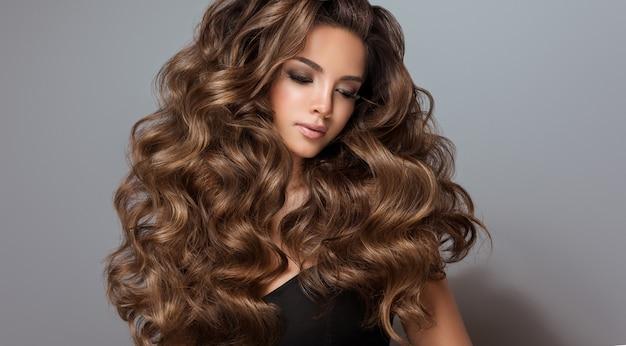 긴 곱슬곱슬한 잘 손질된 머리를 가진 젊은 갈색 머리의 아름다운 모델 우수한 머리 파도 아름다움