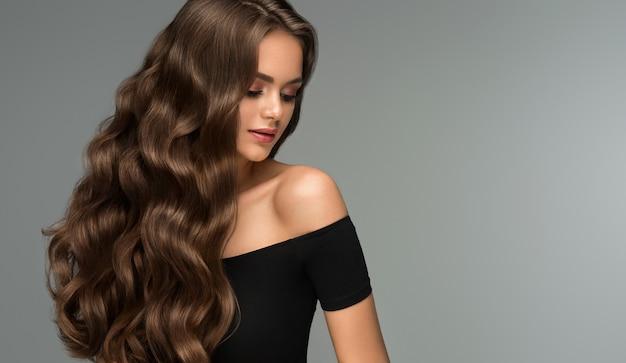 長い巻き毛の手入れの行き届いた髪の若い茶色の髪の美しいモデル優れた髪の波理髪アートとヘアケア