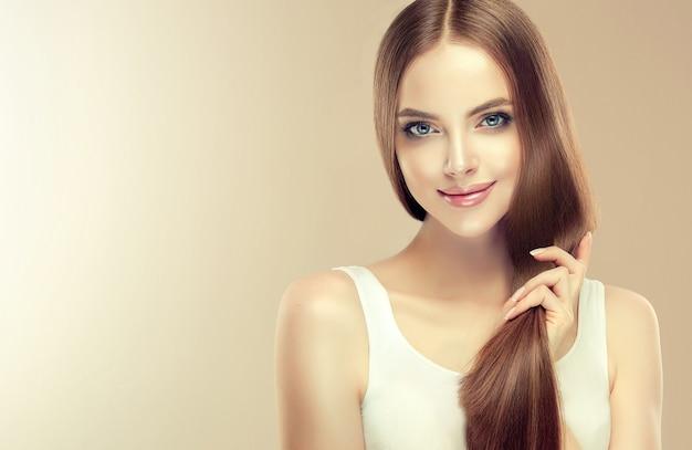 長くてまっすぐな髪の若い茶色の髪の美しいモデルは、手に手入れの行き届いた健康な髪の尻尾を持っています。ヘアケアの自然の美しさと健康。
